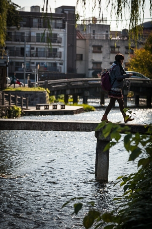 Girl crossing narrow bridge